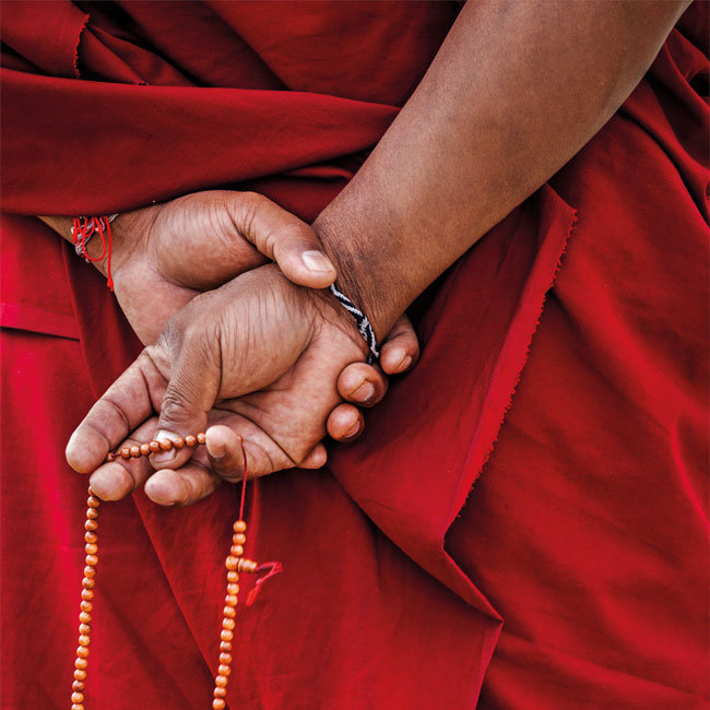 buddhist monk with beads in his hands
